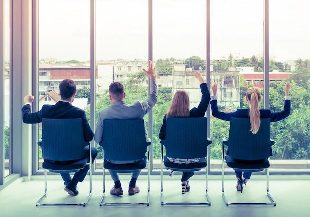 Team van werknemer viert succes aan de vensters