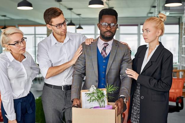 Team van werknemers ondersteunt hun afrikaanse mannelijke collega die het werk verlaat