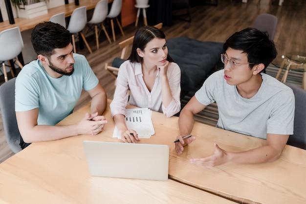 Team van werknemers op kantoor die zaken bespreken met laptop en documenten