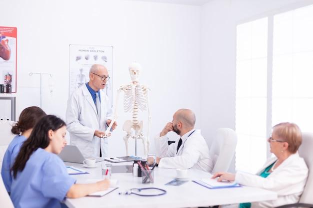 Team van wetenschapper die menselijk skelet in de vergaderruimte onderzoekt en bestudeert om een diagnose te stellen. kliniek deskundige therapeut in gesprek met collega's over ziekte, medische professional.