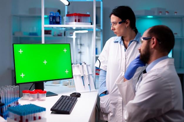 Team van wetenschappers die werken en analyseren met behulp van computer met groen scherm in kliniek, chemisch specialist chemical