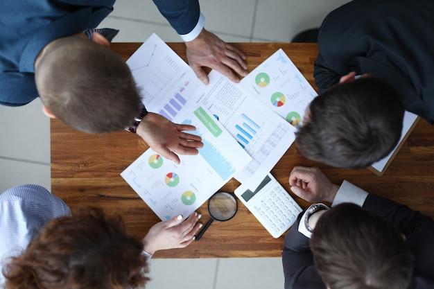 Team van zakenlieden zitten aan tafel en zakelijke cijfers te bespreken. jaarlijkse financiële overzichten concept