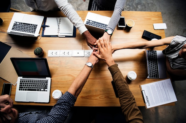 Team van zakenmensen die handen stapelen