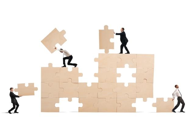 Team van zakenmensen werken samen en werken samen om een puzzel te bouwen