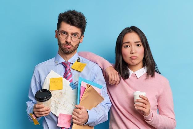 Team werk concept. twee ontevreden vermoeide collega's maakten samen een financieel rapport op, poseren met koffie om verdrietig naar de camera te gaan kijken. studenten hebben een deadline om zich voor te bereiden op het eindexamen aan de universiteit