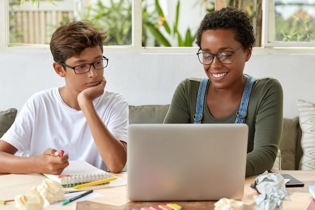 Team werk concept. zwarte slimme vrouwelijke leraar en haar leerling kijken samen naar trainingsvideo, gericht op laptop, verbonden met internet, zitten op het bureaublad met notitieblok voor het maken van records