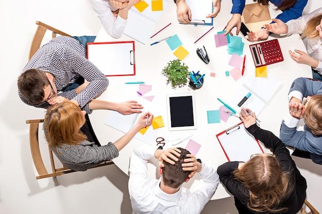 Team zit achter bureau, controleert rapporten, praat. bovenaanzicht. bedrijfsconcept van samenwerking, teamwerk, vergadering
