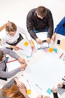 Team zit achter bureau, controleert rapporten, praat. bovenaanzicht. het bedrijfsconcept van samenwerking, teamwerk, vergadering