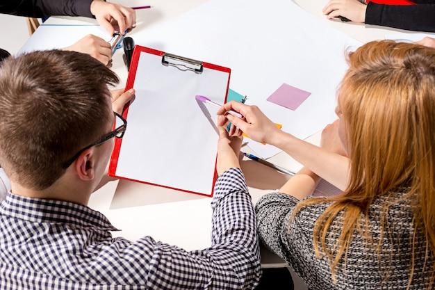 Team zit achter bureau, controleert rapporten, praat. het bedrijfsconcept van samenwerking, teamwerk, vergadering