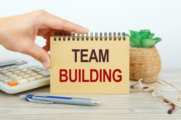 Teambuilding is geschreven op een notitieblok op een bureau met kantooraccessoires.