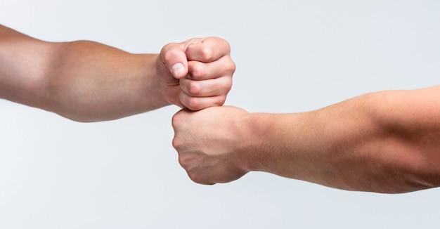 Teamconcept. mensen stoten hun vuisten tegen elkaar, armen. vriendelijke handdruk, vrienden begroeten. twee handen, geïsoleerde arm. handen van man mensen vuist hobbel team teamwork, succes. man die vuist bult geeft.
