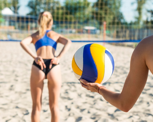 Teamgenoot ontvangt handsignalen van de vrouw vooraan tijdens het volleyballen