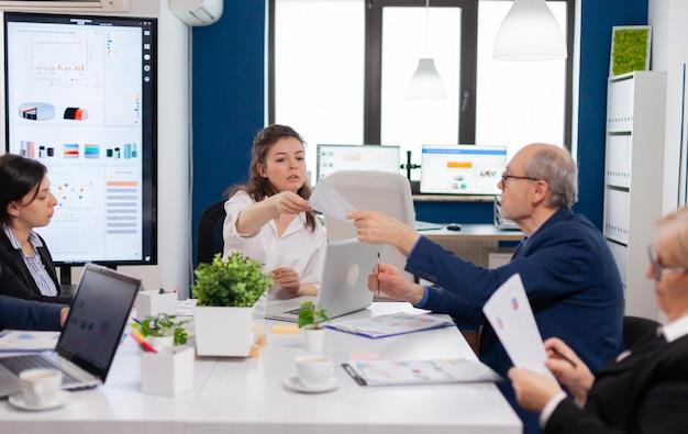 Teamleider van het opstarten van taken voor multi-etnische collega's in de vergaderruimte van het bedrijf