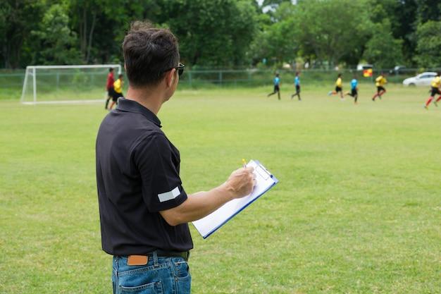 Teammanager coaching zijn bemanning naast voetbal of voetbalveld