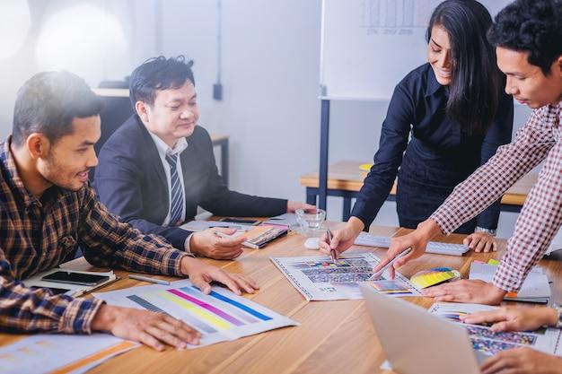 Teamontwerper grafisch werken met kleurenkaart en brainstorm voor nieuw project vergadering.