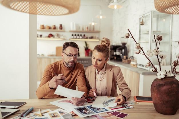 Teamwerk. creatieve modeontwerper die schetsen van zijn nieuwe collectie bespreekt met zijn assistent.