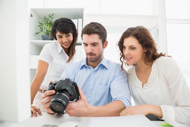 Teamwerk dat digitale camera houdt en op elkaar inwerkt