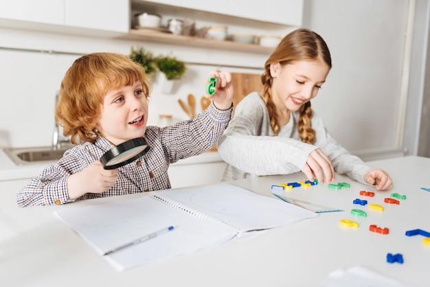Teamwerk. enthousiaste creatieve aardige meid die wat berekeningen uitvoert met behulp van speciale spelnummers terwijl haar broer een van de kleurrijke stukken onderzoekt