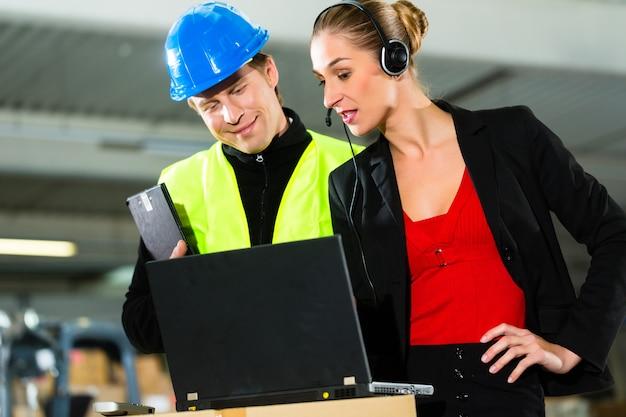 Teamwerk, magazijnier of heftruckchauffeur en vrouwelijke supervisor met laptop, headset en mobiele telefoon, bij magazijn van expeditiebedrijf een vorkheftruck