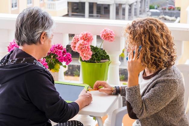 Teamwerk met twee prachtige vrouwen, een van middelbare leeftijd 40 en een derde van 70 jaar oud. gebruik tablet en mobiele telefoon om op een moderne manier thuis over de hele wereld met internet te werken