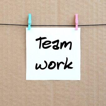 Teamwerk. opmerking staat op een witte sticker die met een wasknijper hangt