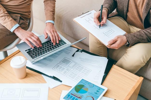 Teamwerk van jonge creatieve programmeurs of ontwerpers van software die werken met online gegevens en papieren per werkplek