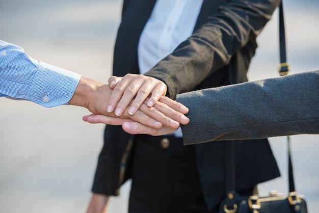 Teamwerk van mensen uit het bedrijfsleven, handen bij elkaar stapelen.