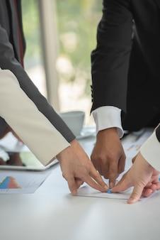 Teamwerk van mensen uit het bedrijfsleven wijzen op het doel op vergadering