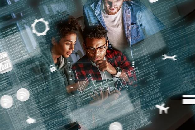 Teamwerk van programmeurs, coderingsbescherming tegen hackaanvallen in navigatiesysteem. satelliet controle. multinationaal team, vrouw en twee mannen