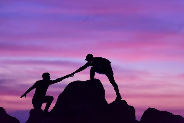 Teamwerk van twee mannen reizigers helpen elkaar op de top van een bergbeklimmen team