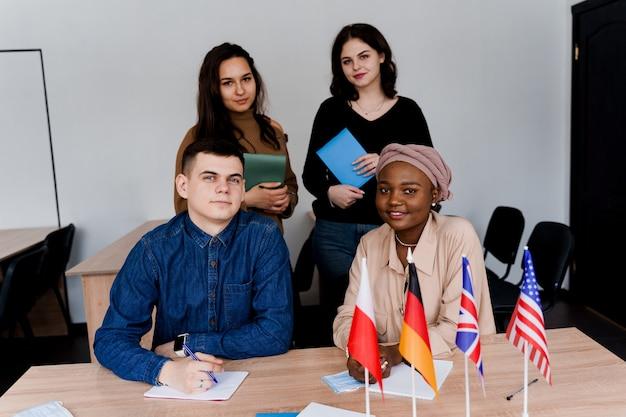 Teamwerk. werken in een multi-etnische groep studenten. leraar studeert samen vreemde talen in de klas. studeren met een notitieboekje. zwarte knappe vrouw student studie met witte mensen samen