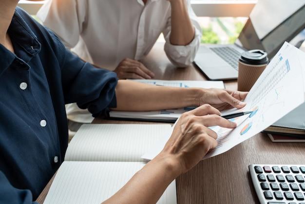 Teamwerkconcept, directeuren die het documentwerk bespreken op vergadering in moderne bureauhal.