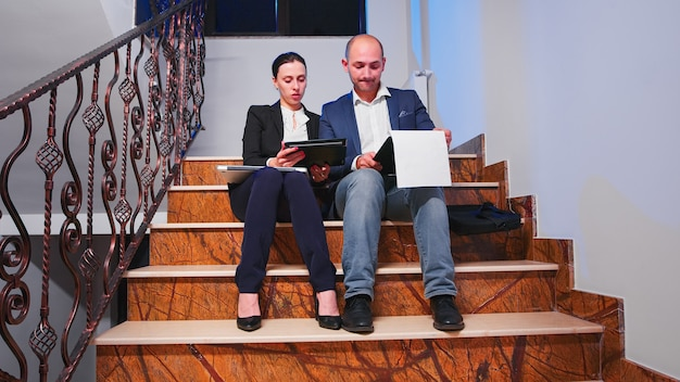 Teamwerkers die op trappen zitten in een bedrijfsgebouw en overuren maken tijdens een financieel project met een deadline, kijkend op tablet en documenten. ondernemers werken laat samen op corporate baan.