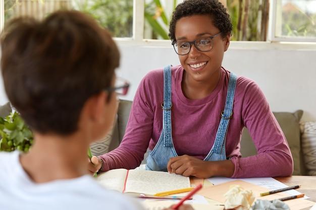 Teamwerkproces. achteraanzicht van groepsgenoten hebben discussie over notitieblok en documenten, zitten op het werk, hebben een blije uitdrukking. positieve afro-amerikaanse vrouw poseren in coworking space met stagiair