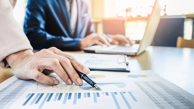 Teamwerkproces. jonge zakenmanagers die werken met een nieuw opstartproject. laptop op houten tafel, toetsenbord typen, sms-bericht, grafiekplannen analyseren.