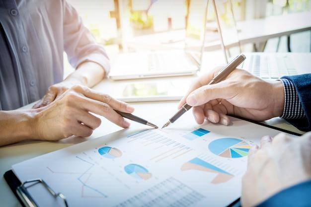 Teamwerkproces. jonge zakenmanagers die werken met een nieuw opstartproject. tablet op houten tafel, toetsenbord typen, sms-bericht, grafiekplannen analyseren