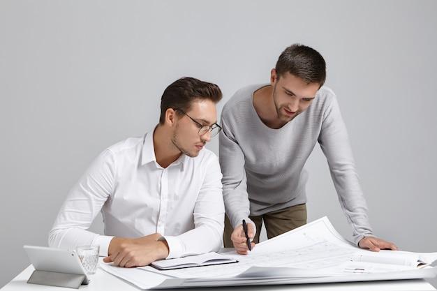 Teamwork, baan en samenwerkingsconcept. foto van twee enthousiaste getalenteerde jonge bebaarde ingenieurs die samenwerken