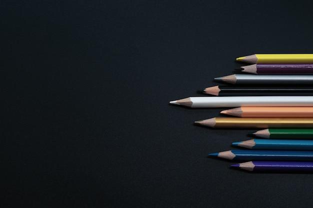 Teamwork concept. groep kleurenpotlood op zwarte achtergrond