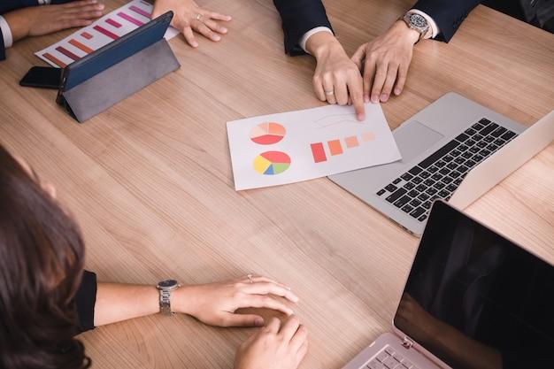 Teamwork met grafiek van de de analysekosten van bedrijfsmensen in vergaderzaal
