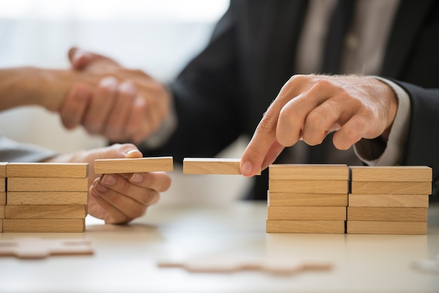 Teamwork of het bouwen van bruggen concept met een zakenman en een vrouw die houten bouwstenen vasthouden om een brug te vormen over een kloof terwijl ze elkaars handen vasthouden