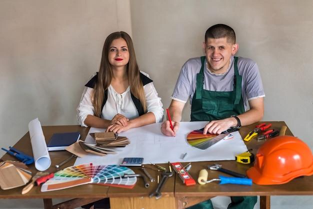 Teamwork op nieuw project, vrouw - ontwerper en man - bouwer