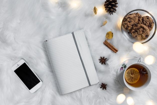 Teatime met notitieboekje en smartphone op plaid