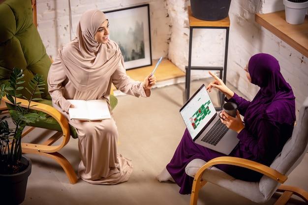 Tech happy en jonge twee moslimvrouwen thuis tijdens les zittend in fauteuils