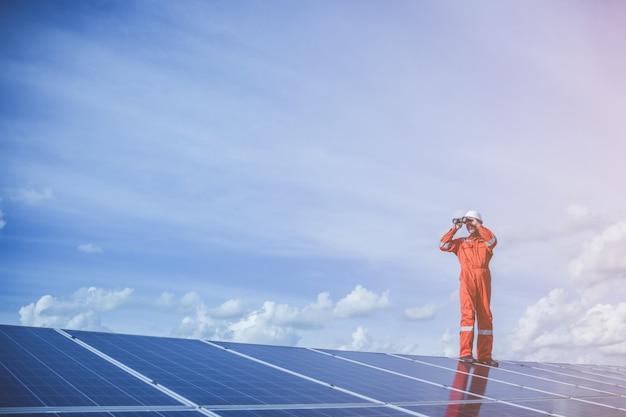 Technici die de opwekkingskracht van een zonne-energiecentrale op een zonnedak bedienen en controleren