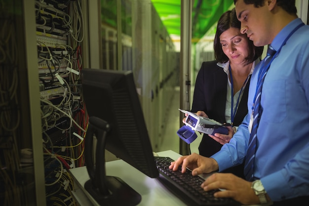 Technici die digitale kabelanalysator gebruiken tijdens het werken op een personal computer