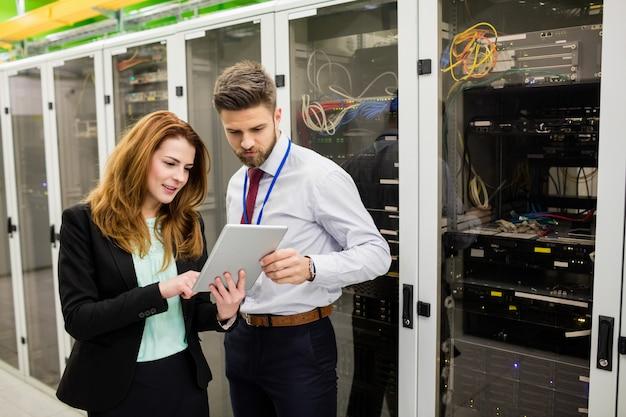 Technici die digitale tablet gebruiken tijdens het analyseren van de server