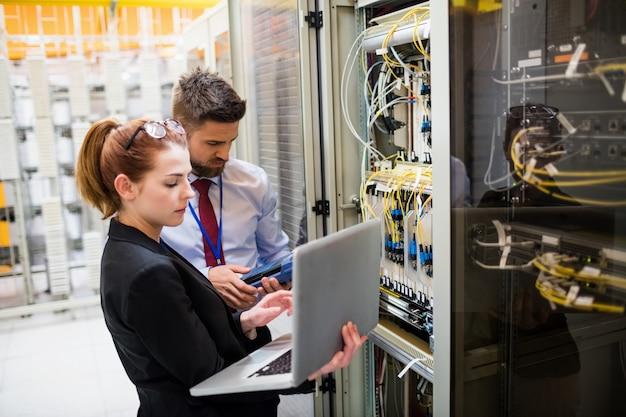 Technici die laptop gebruiken tijdens het analyseren van de server