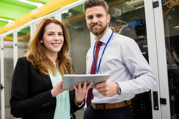 Technici die zich in serverruimte bevinden met digitale tablet