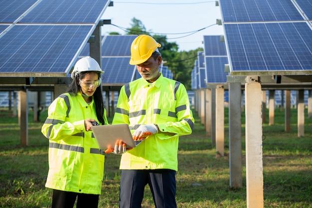 Technici en ingenieur in reflecterende vesten met lange mouwen en veiligheidshelmen bespreken iets over de stroom van zonnepanelen.