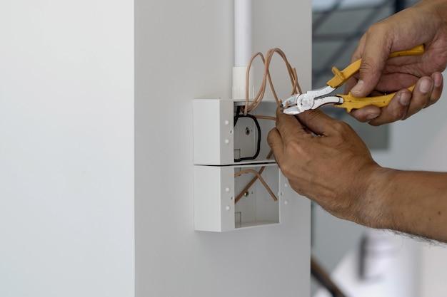 Technici gebruiken een tang om draden af te snijden om pluggen te installeren en schakelt de voordeur in.